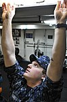 U.S. Navy Seaman Recruit Donald Vines changes a light bulb in the fitness center aboard the aircraft carrier USS Nimitz (CVN 68) 130204-N-JC752-089.jpg