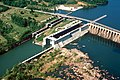 Aerial photograph of the navigation locks at Wilson Dam, with the shore to the left and the dam wall to the right.