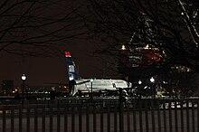 Photo de nuit montrant l'avion, aux couleurs bleues et blanches, sur la berge.