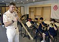 US Navy 031029-N-1693W-003 Seventh Fleet Band member Musician 2nd Class Joseph Dowdy instructs students from Hong Kong International School on the correct way to produce a tone with the trombone during a demonstration class.jpg