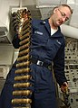 US Navy 040419-N-9621S-006 Fire Controlman 3rd Class Dennis McVicker, of Lansing, Mich., links plugged 20-millimeter dummy rounds for the Close-In Weapons System (CIWS).jpg