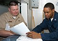 US Navy 040625-N-2382W-064 Chief Aviation Structural Mechanic Mark Brown, from Virginia Beach, Va., reviews his service record with Personnelman 3rd Class Jason Wood.jpg