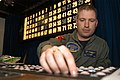 US Navy 041120-N-4584T-002 Aviation Warfare Systems Operator 1st Class Dwayne Cardin assigned to Operations Department assist in the Bingo Night festivities as the bingo facilitator.jpg