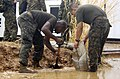 US Navy 050114-N-3642E-001 Marine Corps Lance Cpl. Odell Sampson, left, and Pvt. Xabier Oitizlolon fill sandbags to divert water after heavy rains flooded some of the walkways and roads at Utapao Royal Thai Air Base, Thailand.jpg