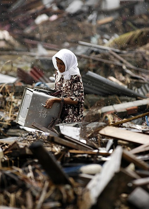 US Navy 050114-N-4166B-017 An Indonesian Woman searches through debris in the rain, where her house once stood, in the city of Banda Aceh on the island of Sumatra, Indonesia