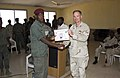 US Navy 061127-N-3884F-071 Captain John Q. Dal Santo, J9 Director, Combined Joint Task Force Horn of Africa, presents a counter-terrorism training completion certificate to Djiboutian army soldier Ibrahim Mohamed Kamil.jpg