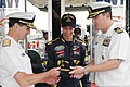 US Navy 070728-N-5362H-052 Rear Adm. Bruce Clingan receives a command ball cap from Cmdr. John Harber, intel officer aboard USS Carl Vinson (CVN 70) during a meet and greet with Navy NASCAR team driver Brad Keselowski.jpg