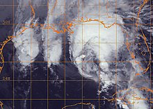 Black and white satellite image of a disorganized tropical cyclone in the Gulf of Mexico. Most of the storm's clouds are displaced to the north in an arc shape.
