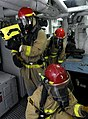 US Navy 100303-N-7280V-509 Sailors use a Naval Firefighting Thermal Imager (NFTI) to asses a simulated casualty during a main space fire drill.jpg