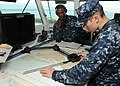 US Navy 100907-N-4997L-034 Quartermaster 3rd Class Tim Hayes, right, from Albany, Ga., uses a parallel motion protractor to plot the coordinates of.jpg