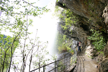 Photograph of a trail under a waterfall