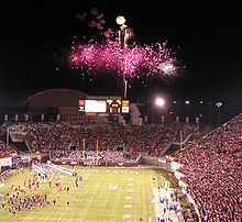 Football players enter a packed stadium with fireworks erupting at one end