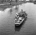 Vrouwen en mannen in een boot op een kanaal in Nickerie, Bestanddeelnr 252-5541.jpg