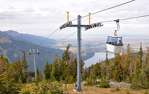 A gondola begins its descent from Mount Howard. Wallowa Lake and the Wallowa Valley are to the right.
