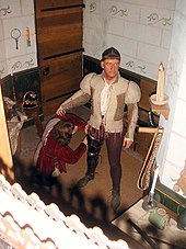A wax figure of a man stands, preparing for battle. The figure sports a bowl cut and wears a khaki doublet and dark brown breeches. At its legs is the wax figure of a kneeling squire.