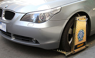 Wheel clamp - A modern wheel clamp placed on a vehicle for a parking violation in Melbourne by the Victorian Sheriff; note the tire spikes and panel preventing the vehicle being driven or the wheel being removed
