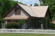 One-and-a-half-story house with gable roof and small front porch; surrounded by picket fence