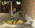Young adivasi woman crushing rice, MP, India.jpg