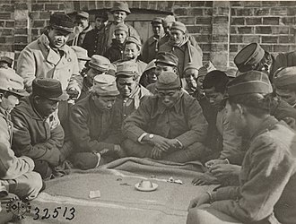 Chuck-a-luck - Workers play Chuck-a-luck during World War One in France on an improvised board.