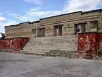 Ruins of a building decorated with geometric patterns in relief. A flight of steps lined by red walls leads to the entrance of the building.