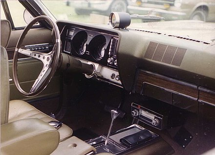 Factory optional 8-track stereo player in a 1967 Marlin American Motors (AMC) vehicle mounted between the center console and dash 1967 Marlin gold ny-inf.jpg
