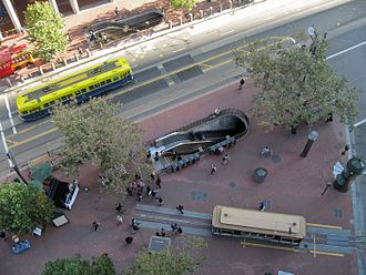Embarcadero station - Market and Drumm with the station entrances in the center and top left. An F Market & Wharves streetcar is running inbound on Market Street (left, just above center) and a cable car waits in the pinch tracks (lower right).