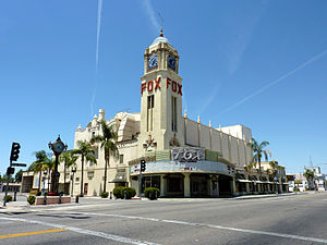 The Fox Theater from the corner of 20th St. and H St. Shows main entrance with neon marquee, and Spanish Revival clock tower.