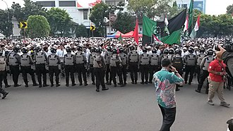 November 2016 Jakarta protests - A group of Indonesian National Police officers (foreground) standing within the protest attendees (background). Several protesters can be seen waving Indonesian flags alongside the flags of their respective Islamist groups.