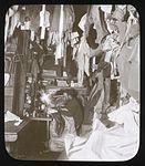 A corner of the hut, Bage mending his sleeping-bag (Australasian Antarctic Expedition, 1911-1914, 1) (6173954058).jpg