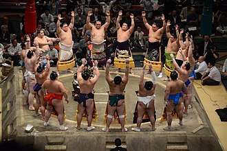 Sumo wrestlers form around the referee during the ring-entering ceremony Aki basho dohyo-iri on Sept. 28 2014.jpg