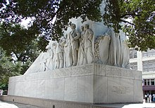 The rectangular base of a cenotaph. An angel is carved on one end. On the side are carvings of several men, shown wearing bucksin or 19th-century suits. Many hold guns or knives; at the far end, one operates a cannon.