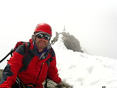 man on summit of mountain wearing alpine climbing equipment