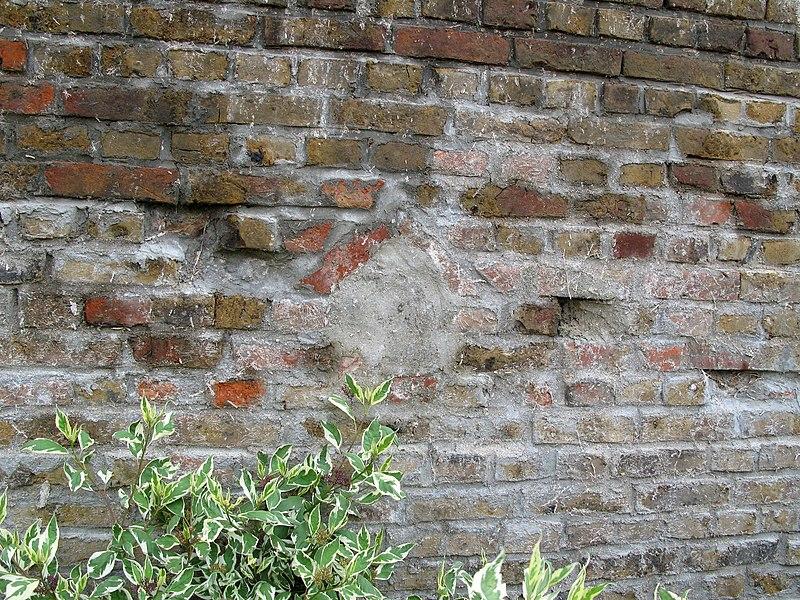 Amiens (Somme, France) - Niche de mitoyenneté dans une propriété (dans l'ancienne cour d'un artisan ou entrepreneur) dans le quartier St-Roch.On remarque bien encore le sommet de la niche, avec ses 2 briques disposées en bâtière.Le mur disposait de 2 niches, à même hauteur. Celle-ci a été comblée entre 1995 et 2000 lors de petits travaux de rejointoiement.