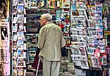 An old man in newsagent's shop, Paris September 2011.jpg