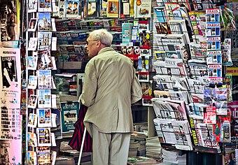 An old man in newsagent's shop, Paris September 2011.jpg