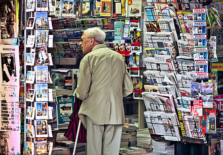 International newspapers on sale in Paris, France An old man in newsagent's shop, Paris September 2011.jpg