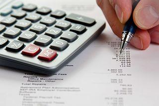 A calculator and a pen on a balance sheet