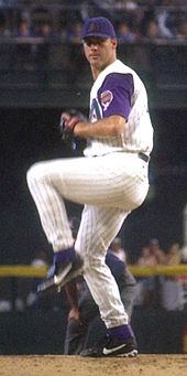 A man in a white pinstriped baseball uniform with purple sleeves and cap stands with his left leg lifted as if about to pitch a baseball.