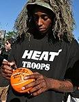 Anthony Mason in sniper garb signs basketball.jpg