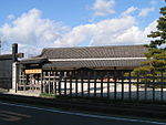 A wide wooden building with a large roof beyond a wooden fence.