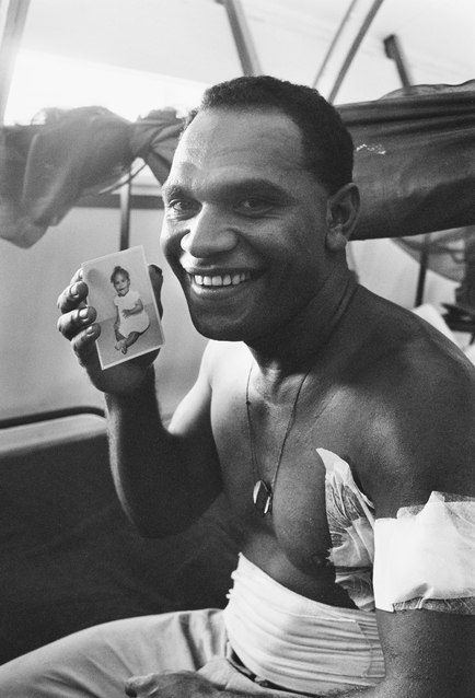 Australian soldier wounded in the Battle of Long Tan holding a photo of his daughter
