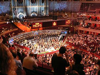 The Proms - The Proms 2005. Most people sit, while Promenaders stand in front of the orchestra. The Royal Albert Hall Organ is in the background.