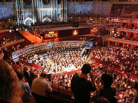 The Proms 2005. Most people sit, while Promenaders stand in front of the orchestra. The Royal Albert Hall Organ is in the background. BBC Proms 31.jpg