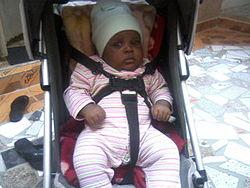 Baby on stroller safely held by belt.jpg