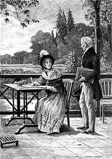 Un homme s'adresse à une jeune femme en train d'écrire à sa table sur une terrasse qui domine un parc.