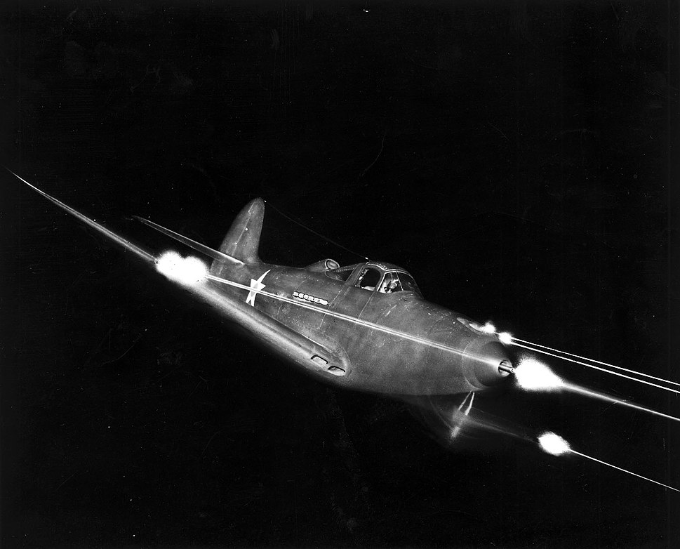 Bell P-39 Airacobra in flight firing all weapons at night