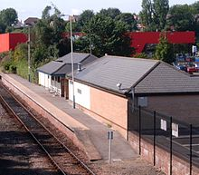 In the foreground is a single storey building with a pitched roof. A railway platform runs along the length of the building. In the background is a large red warehouse style building.