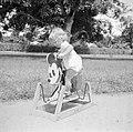 Blond kindje op Mickey Mouse hobbelpaard in Suriname, Bestanddeelnr 252-6871.jpg