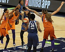 Very tall woman with arms raised, young woman passing the ball forward under strain, surrounded by players