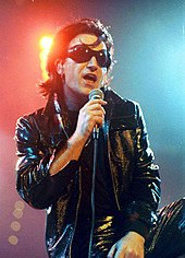 Bono with black hair, black sunglasses, and a black leather attire speaks into a microphone.